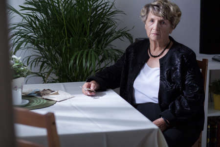 ojos tristes: Elderly woman sitting at the table at home