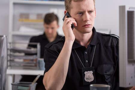 Politieman praat op mobiele telefoon Stockfoto