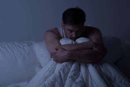 ansiedad: Hombre desdichado con trastorno de ansiedad que se sienta en la cama asustado