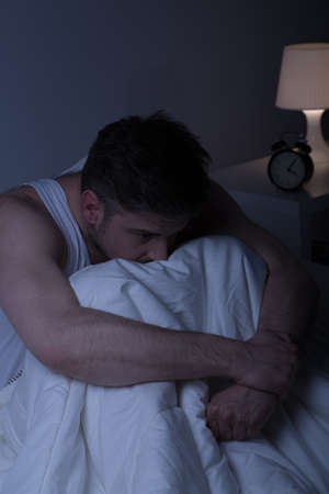despaired: Depressed man sitting alone in bed at night Stock Photo