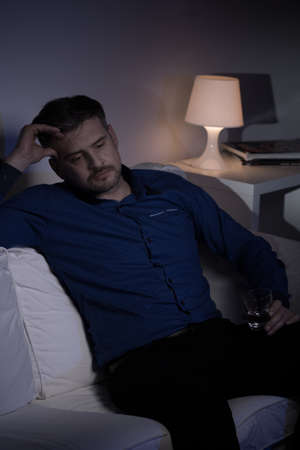 despaired: Alcoholic man drinking vodka alone in the evening