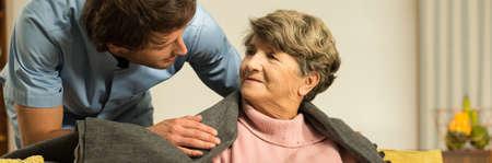 Male helpful caregiver taking care of senior woman