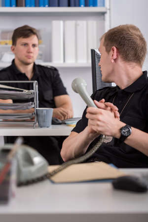 police station: Policeman is talking on stationary telephone at work Stock Photo