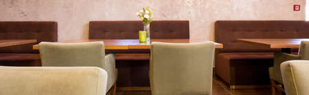 comfort room: Restaurant dining tables and comfortable quilted couches Stock Photo