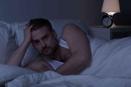 gente durmiendo: Hombre slepless cansado para mantenerse despierto en la cama Foto de archivo