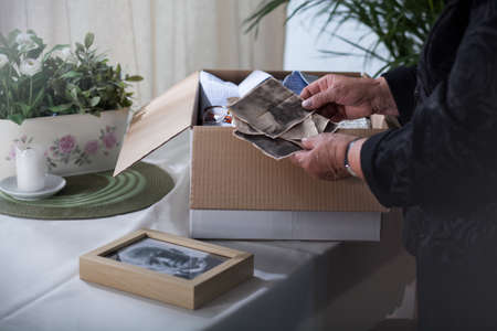 old hand: Close-up on old photographs in the hands of widow