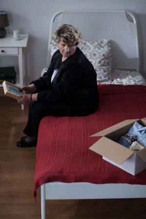 widow: Sad widow sitting on bed and holding picture