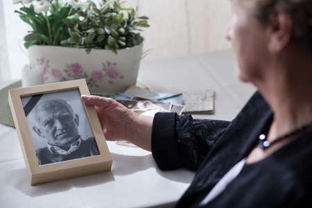 Widow looking at the photo of her dead husband