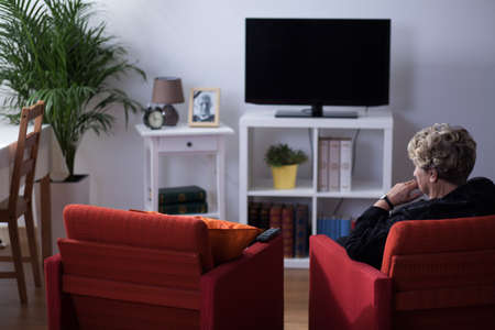 elderly: Pensive widow sitting alone in living room
