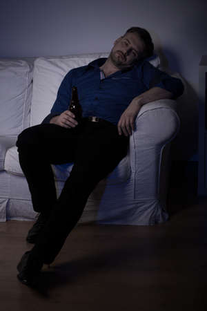 miserable: Miserable drunk man with a bottle of beer