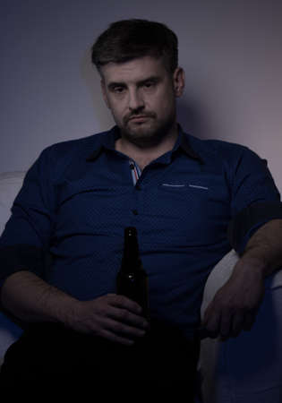 miserable: Tired miserable man drinking beer alone at home