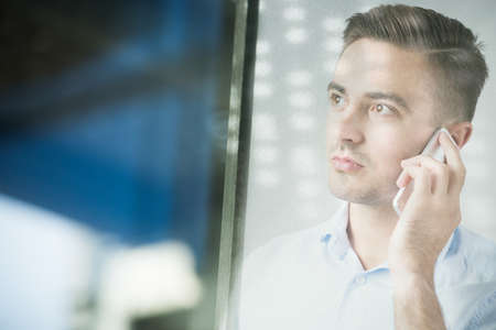exposed: Double exposed man talking on mobilephone at work
