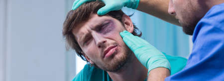 black eye: Young man with black eye in emergency room Stock Photo