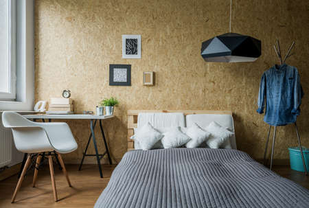 Cozy teenage bedroom with trendy wooden wall Stock Photo