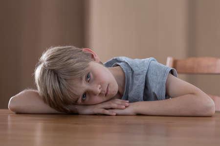 child portrait: Sad worried boy lying on the table