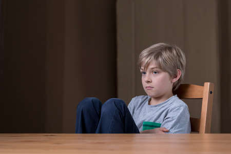 offended: Offended little child sitting at the desk