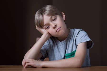 niños sentados: Preocupado niño pequeño sentado en el escritorio