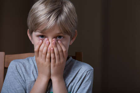 child portrait: Afraid blonde young boy covering his mouth