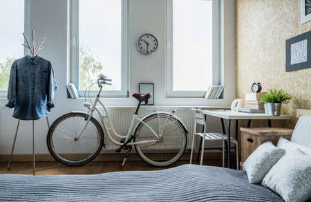 minimalist apartment: Trendy white city bicycle in bright bedroom
