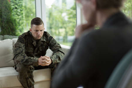 Photo of worried handsome soldier during counseling session