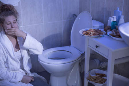 bulimia: Teenage bulimic girl vomiting in the bathroom