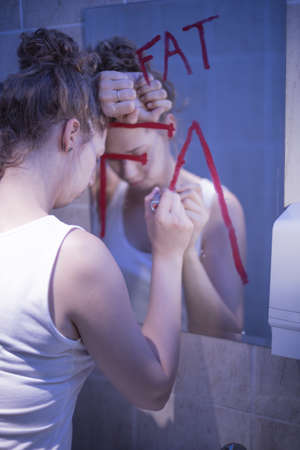 anorexia girl: Girl with complexes is writing on mirror Stock Photo