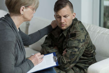 traumatic: Picture of psychiatrist helping war veteran to overcome trauma Stock Photo