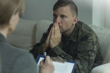 Photo of depressed soldier on consultation with psychoanalyst