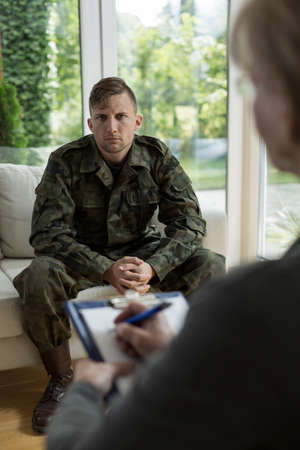 diagnosing: Photo of female therapist diagnosing soldier suffering from trauma