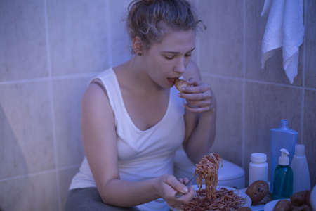 Teenage bulimic girl is eating in bathroom