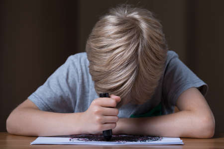 child sad: Depressed sad schoolboy drawing only black crayon Stock Photo