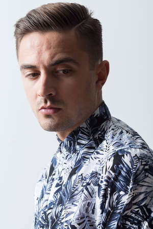 unhappiness: Portrait of young man in floral shirt
