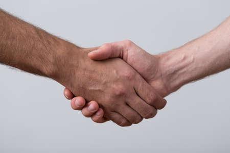 personas saludandose: Primer plano de las personas dándose la mano sobre fondo gris