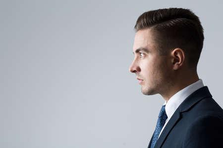 Profiel van jonge ondernemer op een grijze achtergrond Stockfoto