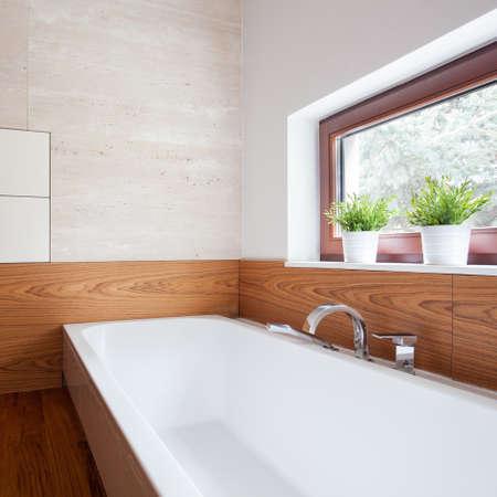 room decor: White porcelain bath in modern wooden washroom
