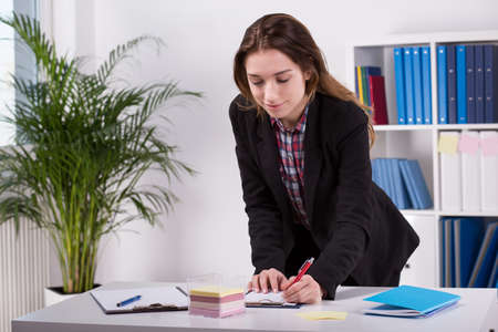 writes: Picture of a female worker writing down her ideas