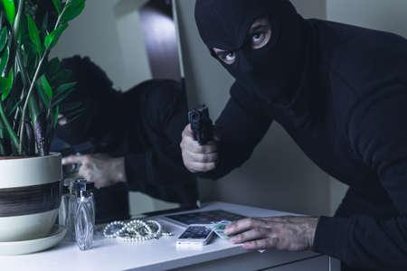 robbing: Photo of masked intruder with gun robbing money Stock Photo
