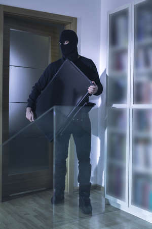 plunder: Photo of robber in black mask and his plunder