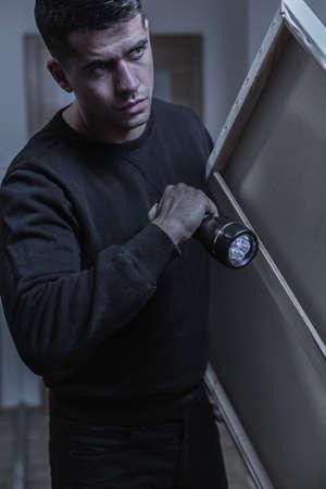 loot: Photo of burglar with flashlight and his loot