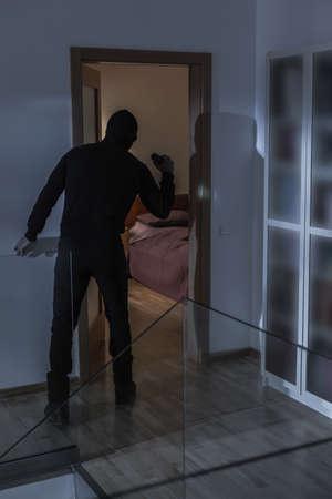 plunder: Image of robber in black costume during mugging in villa