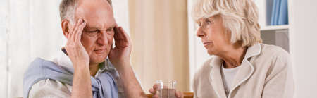 parejas amor: El hombre mayor con dolor de cabeza consigue un vaso de agua Foto de archivo