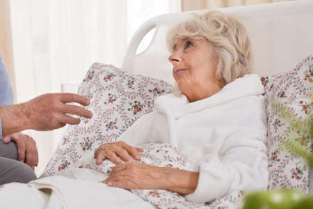 wife and husband: Ill senior woman lying in bed and resting