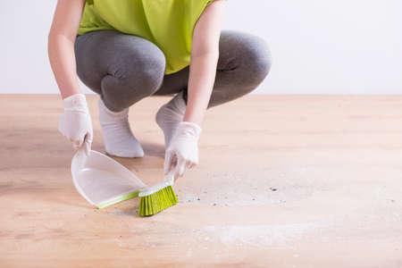 housekeeper: Imagen de la ama de llaves con guantes de suelo de madera de barrido