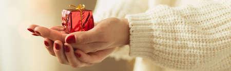 dar un regalo: Closeup of small christmas present on woman hands