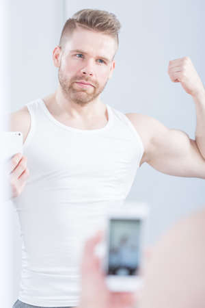muscular male: Narcissistic sporty man taking picture of himself Stock Photo