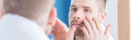narcissism: Young man looking at his wrinkles - panorama