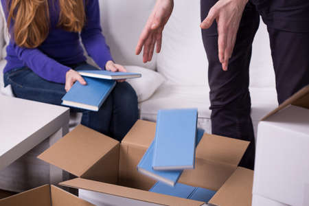 put up: Close up of man and woman putting things in box