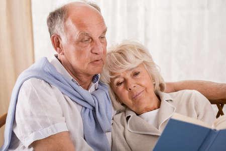 embracing couple: Elegant senior couple reading a book together