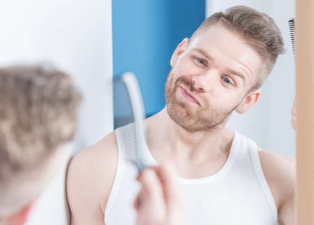 stubble: Metrosexual guy with comb in the bathroom