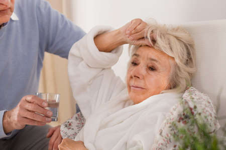 Husband taking care of his elderly sick wife Stock Photo - 48338320